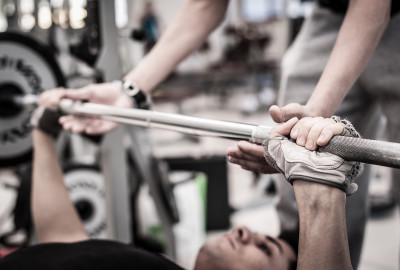 Young man lifting the barbell in the gym with instructor. Focus on hand.